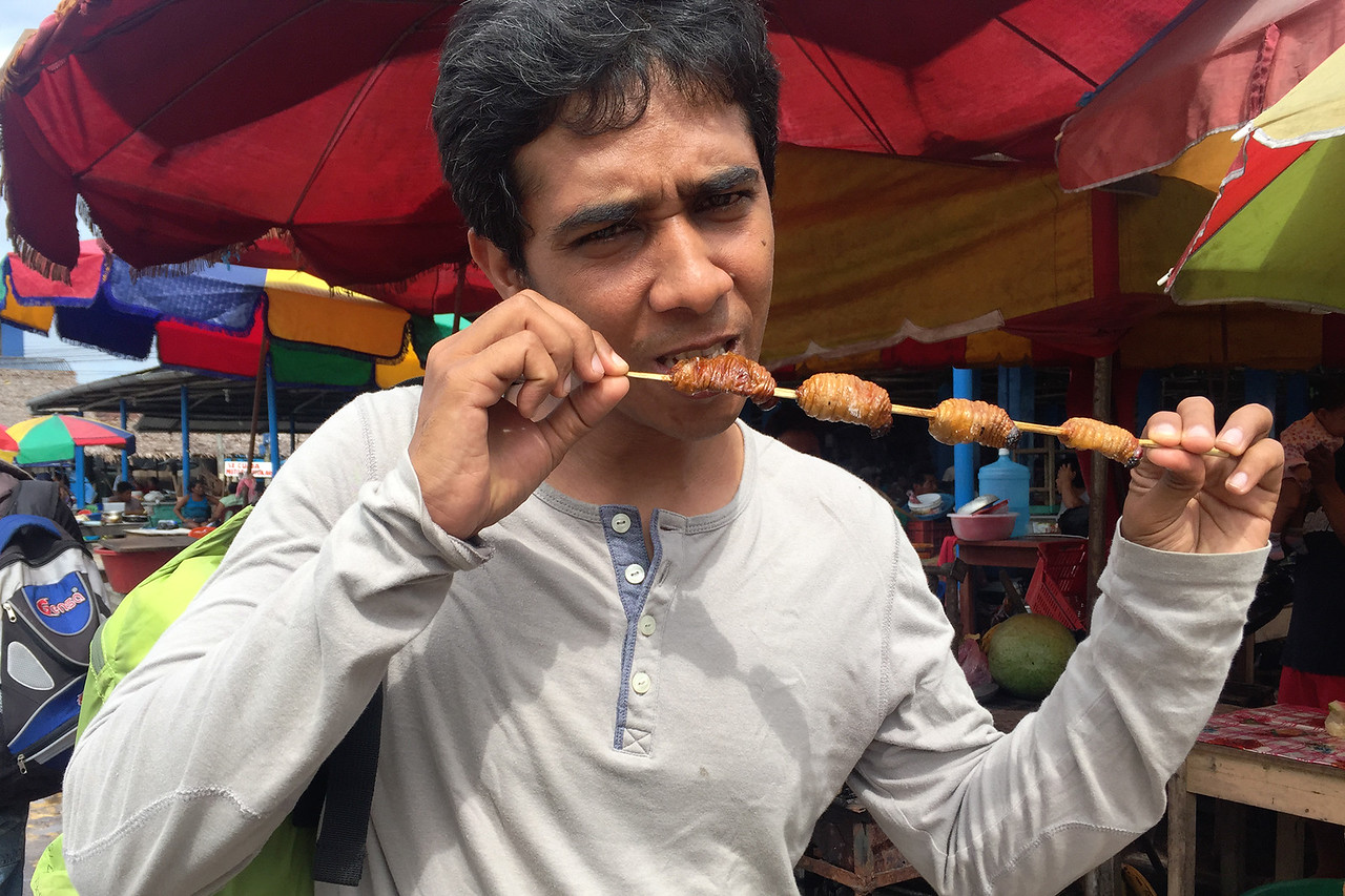 Tasting the suri worms at Nannay port en route the Amazon forest, Peru