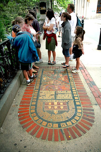 A spot on the sidewalk marking the site of America's first public school.