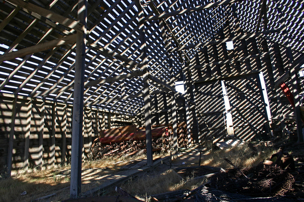 The main structure of a barn in the Palouse seems strong , but time and weather have stripped it of its roof allowing the bright sunlight to make dizzying patterns.