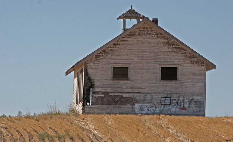 Stilll standing in spite of a fire and with graffiti marked walls a small school house waits for the students who will not arrive..