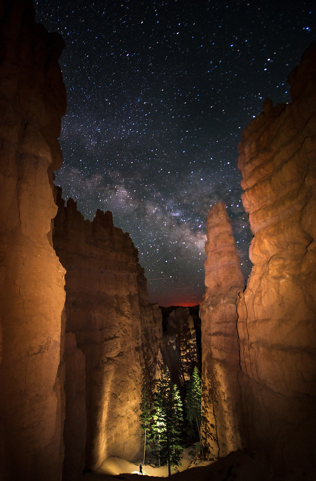 A hiker navigates his way through towering hoodoos while the Milky Way shines bright overhead.  Bryce Canyon, Utah.  JumpingBorders.com