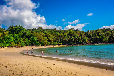 Tropical beach in Manuel Antonio National Park with tourists in Costa Rica