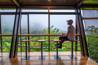 Tourist sitting in the lounge bar of Celeste Mountain Lodge in Costa Rica