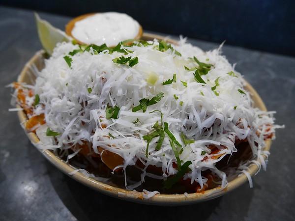 Nopalito: Totopos con chile-tortilla chips, salsa de arbol, cotija cheese, onions, cilantro, crema and lime