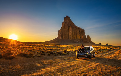 Boy enjoys sunset at Shiprock sitting on the hood of his car
