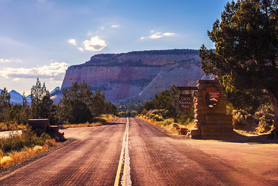 Road and welcome sign at the entrance to Zion National Park before sunset