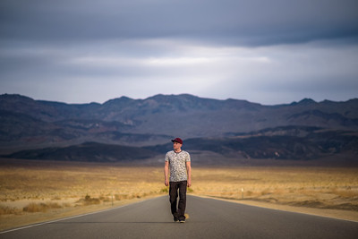 Young man walking alone through an empty street in the desert of Death Valley
