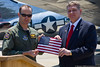 Major Scott Clyman, Air Force Reserve F-16 pilot and museum trustee, presents a flag to  Michael Sulick. Clyman carried the flag during a mission in support of the attack on the CIA employees in Afghanistan.
