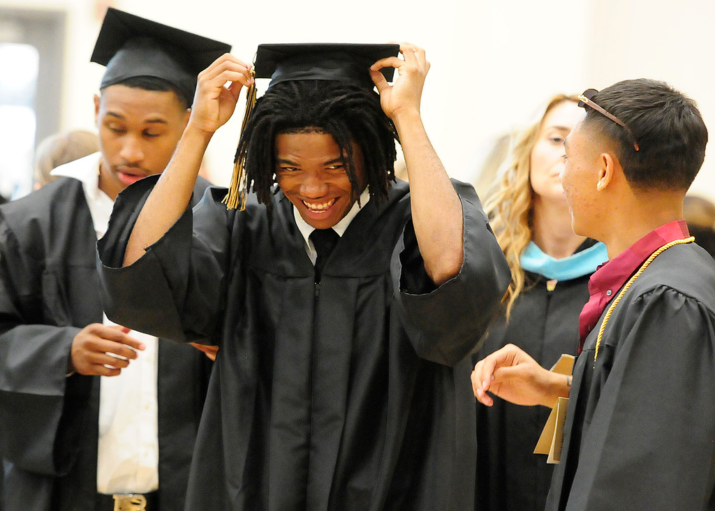 . AMERICAN CANYON, CA - JUNE 6, Robbi Brown smiles has he hangs two tassles off his cap as he prepares to graduate from American Canyon High School on Wednesday. (CHRIS RILEY/TIMES-HERALD)