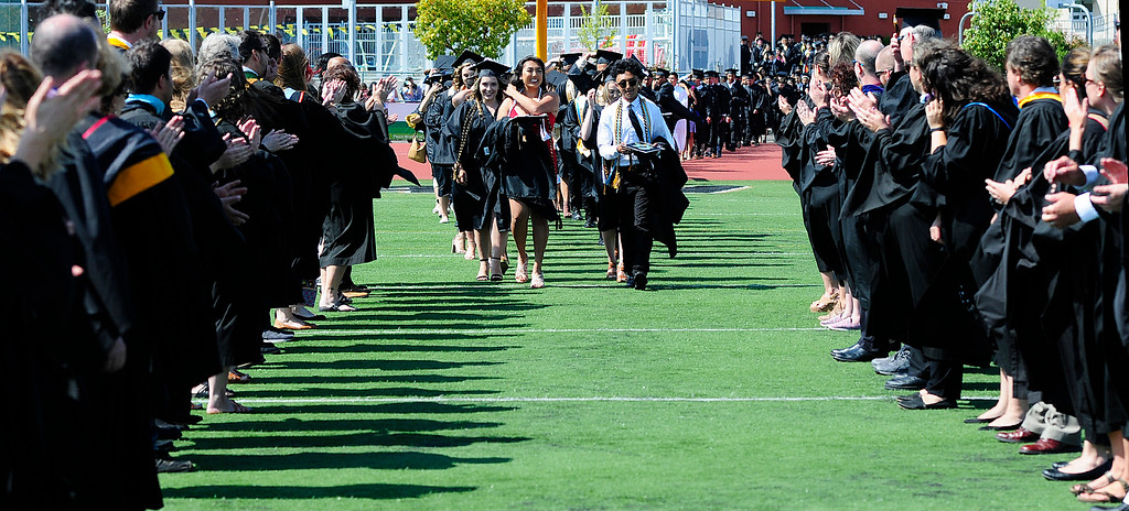 . AMERICAN CANYON, CA - JUNE 6, Graduates walk on to the football field through lines of clapping faculty during graduation at American Canyon High School on Wednesday. (CHRIS RILEY/TIMES-HERALD)