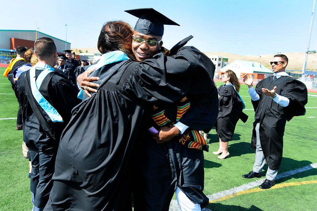 . AMERICAN CANYON, CA - JUNE 6, LaVar Seay gets a hug from a member of the faculty during graduation at American Canyon High School on Wednesday. (CHRIS RILEY/TIMES-HERALD)