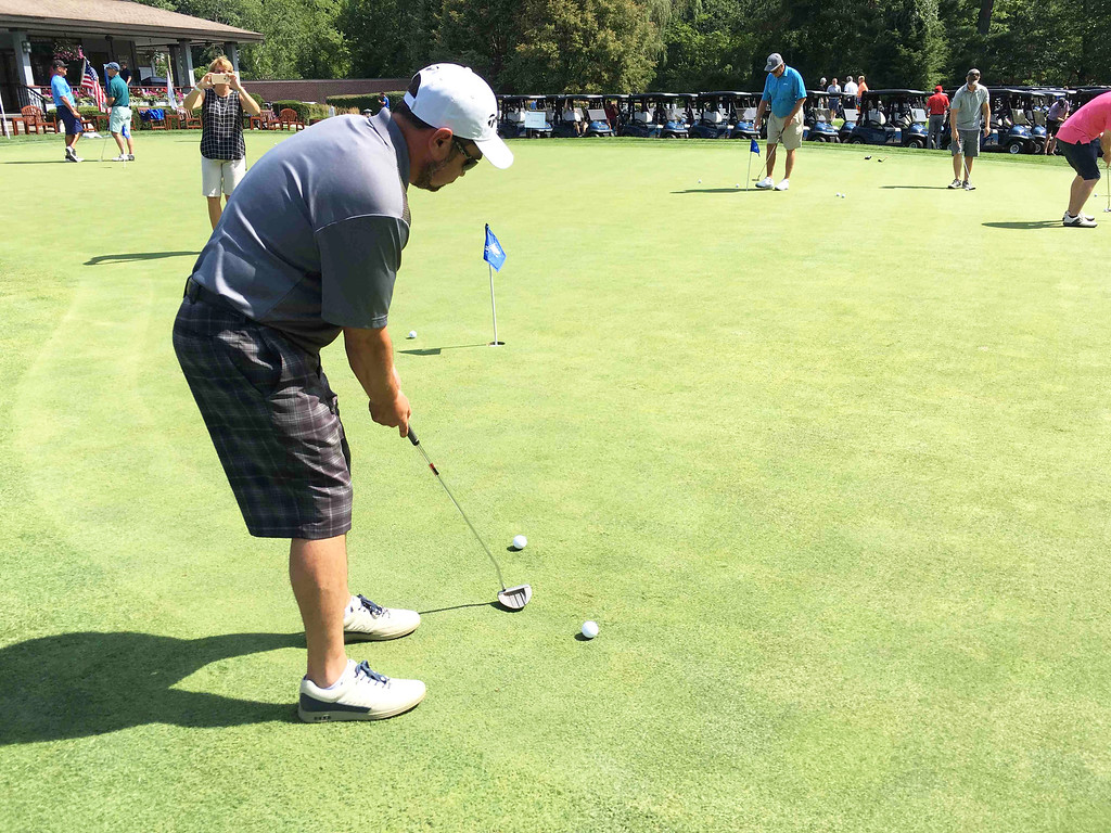 . Golfers practice their putting.