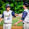 From left, Lowell's American Legion player Fred Kazalski fist bumps his teammate afer making it safe to first base. SUN/Caley McGuane