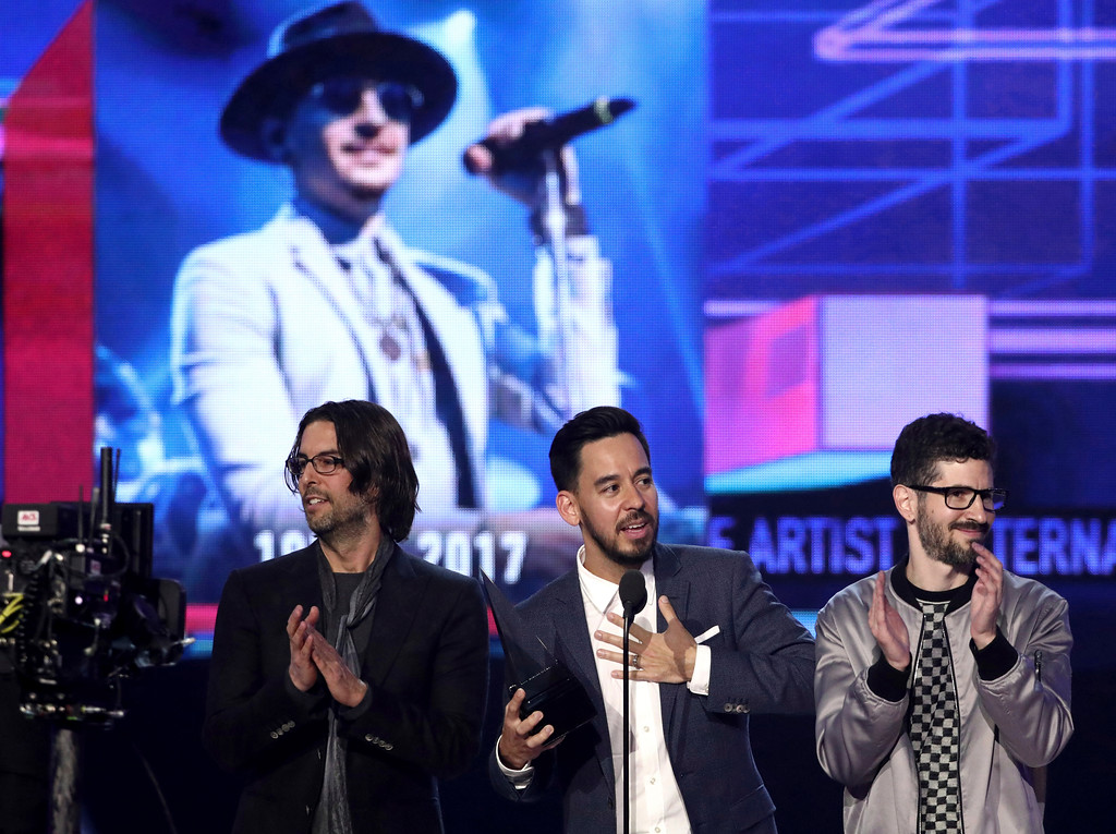 . Rob Bourdon, from left, Mike Shinoda, and Brad Delson of Linkin Park accept the award for favorite artist alternative rock at the American Music Awards at the Microsoft Theater on Sunday, Nov. 19, 2017, in Los Angeles. Pictured on screen is late member Chester Bennington. (Photo by Matt Sayles/Invision/AP)
