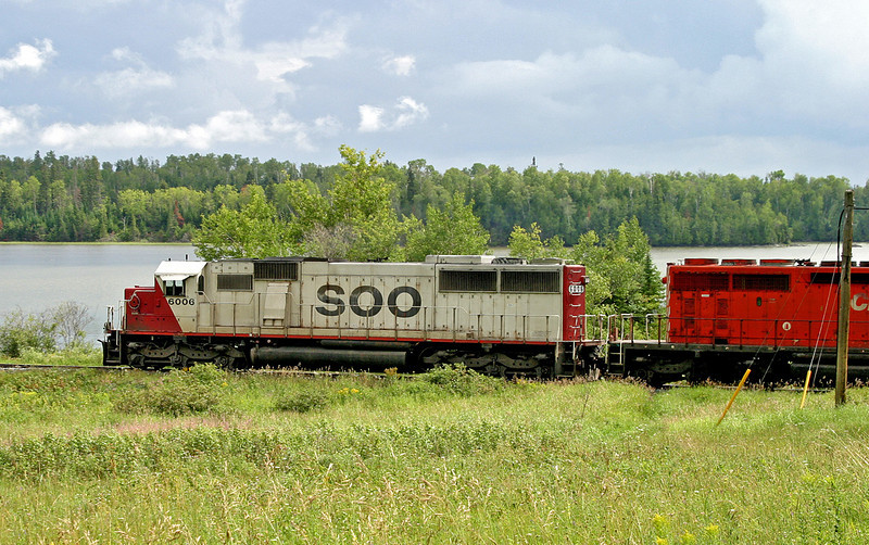 A SOO SD-60, a CP SD-40-2 5658, and off frame another SOO SD-60 6011 pull a train through Wabigoon, Ontario early August of 2003.