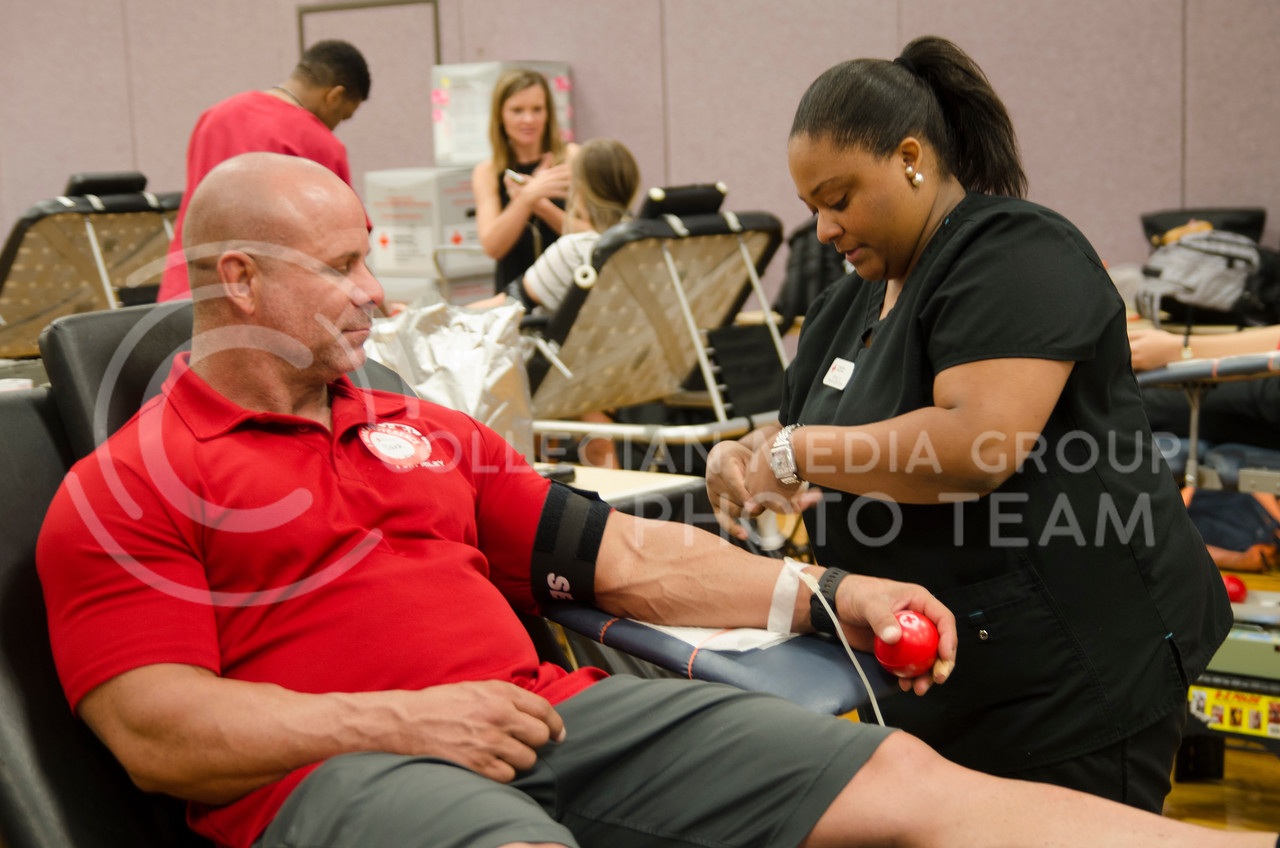Nikkia Mukey, a American Red Cross nurse, draws a blood from a volunteer Mark Bacon during Red Cross fall blood drive at K-State Union on September 25, 2017 (Saya Kakim | Collegian Media Group)