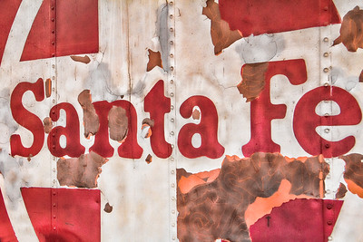 Rusted and faded a vintage Santa Fe Railroad car now serves as part of an eating establishment in the small artistic town of Madrid, New Mexico.  Santa Fe Vintage Railroad Sign by Steven Bateson.