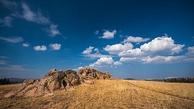 red rocks yellow grass blue sky white clouds Wyoming