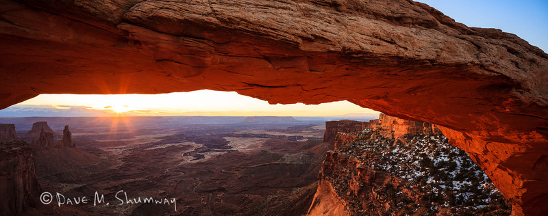 "Mesa Arch glows as the rising sun bursts over a bank of clouds, in Canyonlands National Park, near Moab, Utah. Captured with a Canon 5D II and 24/3.5L T/S II in manual mode at ISO200, f/13, and 1/15th of a second. The camera was mounted on a Gitzo 3541 XLS with an Arca-Swiss Z1sp ballhead. The camera and lens were shifted 12mm (oppositely) to capture a three image ""stichless"" panorama of the scene."