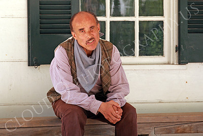 AMER-Slaves 00014 A male slave historical re-enactor sitting on a bench on his owners front porch, by Peter J Mancus