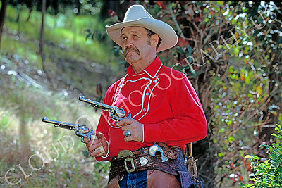 HR-ACB 00003 American cowboy historical reenactor holding two fancy engraved silver pistols by Peter J Mancus
