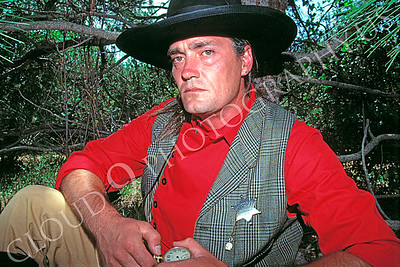 HR-ACB 00005 American cowboy historical reenactor with watch sitting under a tree by Peter J Mancus