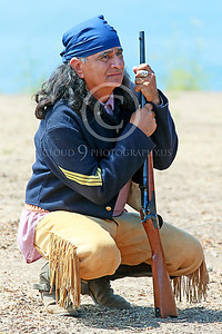 HR-USAIS 00001 A western frontier type US Army Indian scout with rifle squats as he sizes up the situation, historical re-enactor picture by Peter J Mancus
