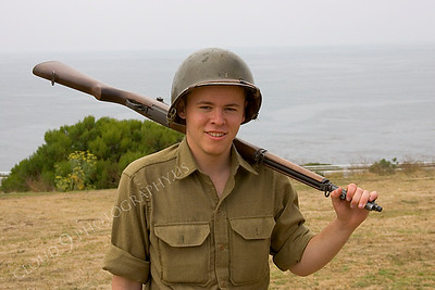 HR-USWWIIA 00004 A young US World War II Army soldier reenactor above a coastline, with rifle and a smile, as if he survived D-Day, by Peter J Mancus