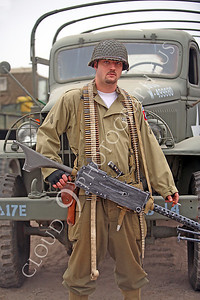 HR - USAWWIIP 00015 A heavily armed paratrooper re-enactor with his machine gun, ammo belt, and smoke, by Peter J Mancus