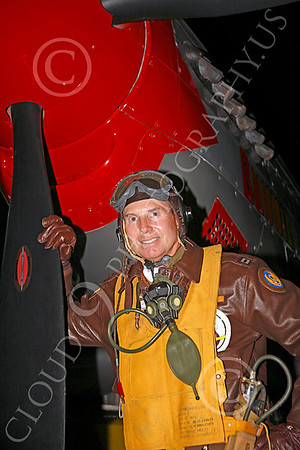 HR - USAAFWWIIAC 00005 A US Army Air Force P-51 Mustang pilot historical reenactor stands by his plane's red nose, at night, before an early morning mission, by Peter J Mancus