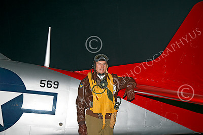 HR - USAAFWWIIAC 00004 A US Army Air Force P-51 Mustang pilot historical reenactor stands by his plane's red tail, at night, before an early morning mission, by Peter J Mancus