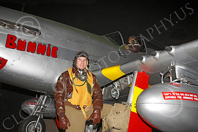 HR - USAAFWWIIAC 00008 A US Army Air Force P-51 Mustang instructor pilot historical reenactor stands by a P-51 with a black pilot in the cockpit, by Peter J Mancus