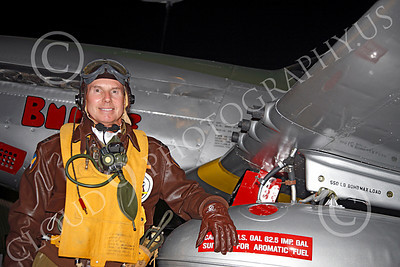 HR - USAAFWWIIAC 00003 A US Army Air Force P-51 Mustang pilot historical reenactor stands by three of his plane's machine guns and a fuel tank, at night before, an early morning mission, by Peter J Mancus