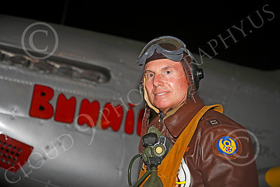 HR - USAAFWWIIAC 00006 A US Army Air Force P-51 Mustang pilot historical reenactor stands by his plane's nose, at night, before an early morning mission, by Peter J Mancus