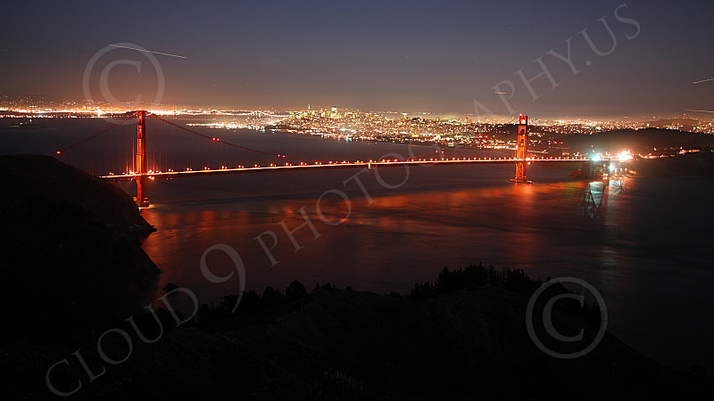 ENGF-GGB 00069 An expansive, elevated, night view of the Golden Gate Bridge with San Francisco in the background and four airplanes' light trails, by Peter J Mancus