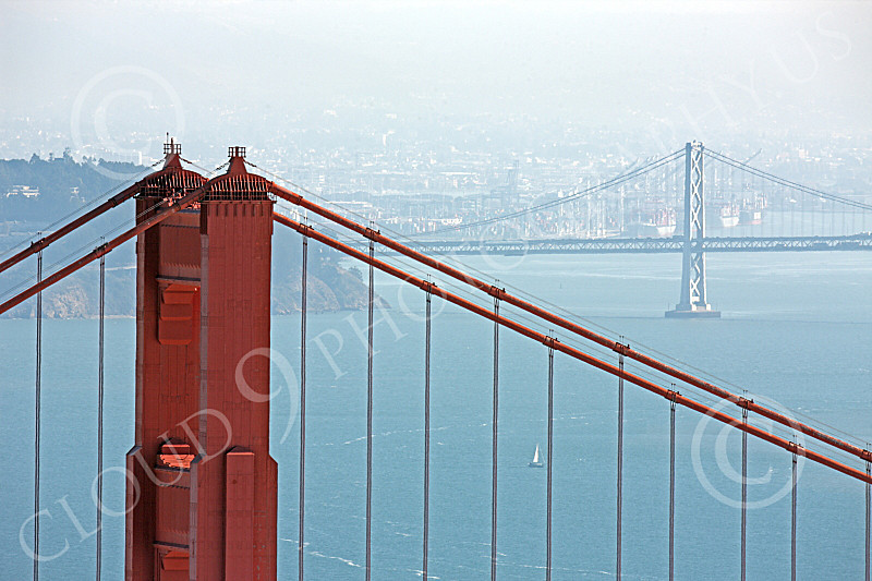 ENGF-GGB 00208 A tight crop of the top of the Golden Gate Bridge's north tower with the Bay Bridge in the background, by Peter J Mancus
