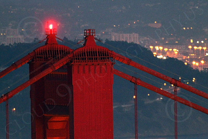 ENGF-GGB 00188 A tight crop of the top of the Golden Gate Bridge's Marin side tower, at night, with Oakland in the background, by Peter J Mancus