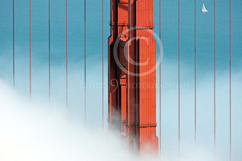 ENGF-GGB 00134 A tight crop of northern Golden Gate Bridge tower arising from fog with a solo sailboat in the background, by Peter J Mancus