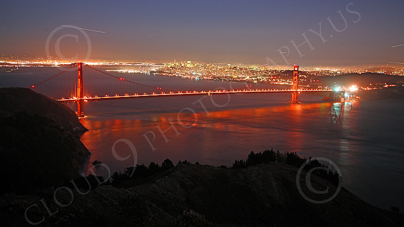 ENGF-GGB 00194 An expansive, elevated, night view of the Golden Gate Bridge with San Francisco in the background and four airplanes' light trails, by Peter J Mancus