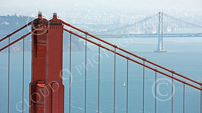 ENGF-GGB 00146 A tight crop of the top of the Golden Gate Bridge's north tower with the Bay Bridge in the background, by Peter J Mancus