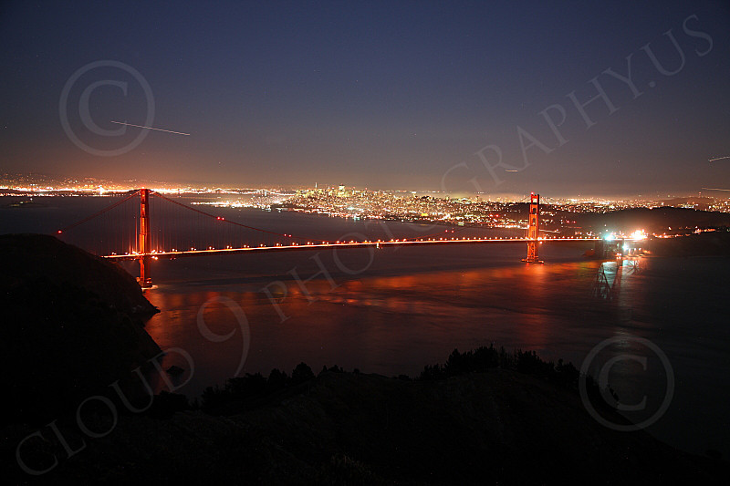 ENGF-GGB 00186 An expansive, elevated, night view of the Golden Gate Bridge with San Francisco in the background and four airplanes' light trails, by Peter J Mancus