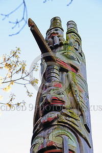 TotPol 00015 A tall, weathered, moss laden, totem pole with a big nose and two human figures on top, totem pole detail picture by Peter J  Mancus