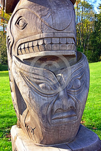 TotPol 00029 A totem pole with a fish inspired shape on top and a sinister stylistic face on the bottom, unpainted wood, detail, totem pole picture by Peter J  Mancus