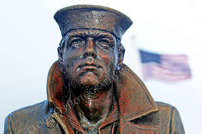 STY - The Lone Sailor 00013 The Lone Sailor statute stands tall under a drizzle with the United States flag in the background, by Peter J Mancus
