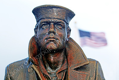 STY - The Lone Sailor 00010 The Lone Sailor statute stands tall under a drizzle with the United States flag in the background, by Peter J Mancus