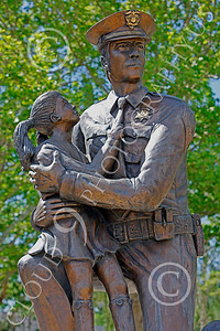 LEOSTY 00005 A kneeling sworn peace officer comforts a little girl who holds onto his tie, by Peter J Mancus