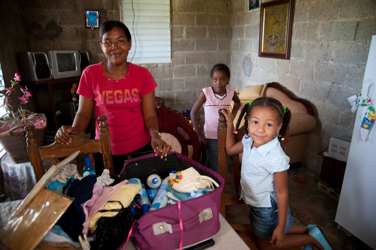 "This is what the loans enable -- this mother has 2 daugthers she supports by selling clothes out of the suitcase.  She was very proud of her ""portable"" business."