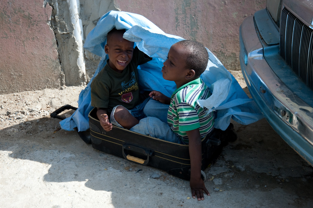 2 kids were playing outside the microfinance meeting while their parents are inside