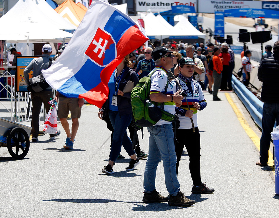 . Valtor and Andrea Hrebik fly the Slovakia flag in support of Slovakian riders at the Stage 3 finish at Laguna Seca Raceway in Monterey on Tuesday, May 15, 2018 during the Amgen Tour of California.  (Vern Fisher - Monterey Herald)