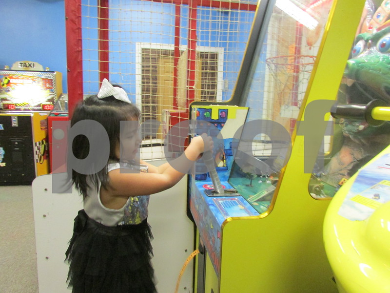 Marie Tavera, 4, plays a game Friday at her parents' new arcade, Amigos Arcade, at 122 S. First St. in DeKalb.